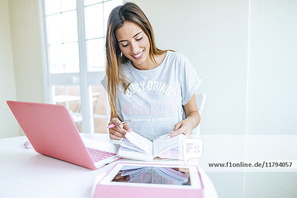 Lächelnde junge Frau schaut auf die Agenda