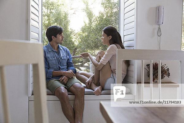 Junges Paar spricht auf der Fensterbank