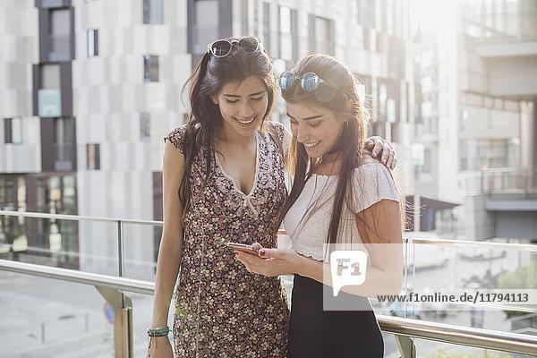 Zwei lächelnde junge Frauen beim Blick auf das Handy in der Stadt