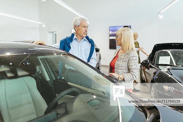 Paar schaut auf Auto in Dealeship