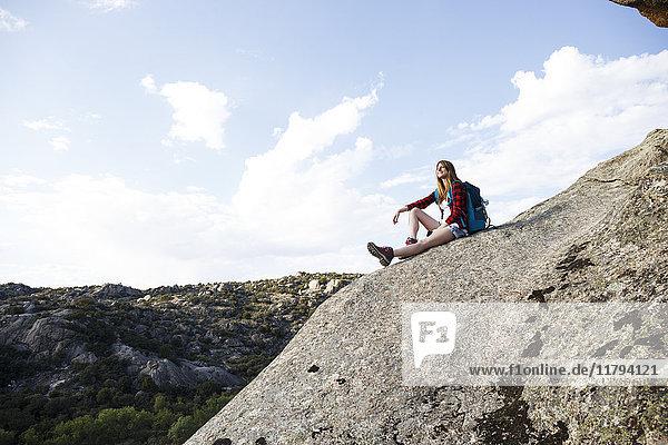 Spanien  Madrid  junge Frau auf einem Felsen während eines Trekking-Tages