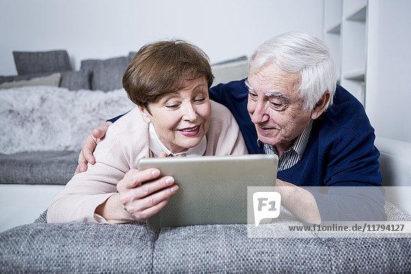 Seniorenpaar auf der Couch liegend mit digitalem Tablett