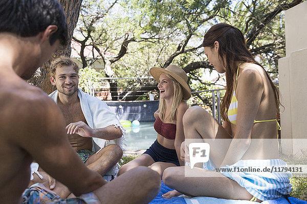 Gruppe von glücklichen Freunden  die sich im Garten am Pool entspannen.