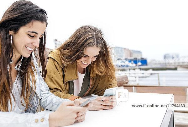 Zwei glückliche junge Frauen  die mit ihren Smartphones Nachrichten senden