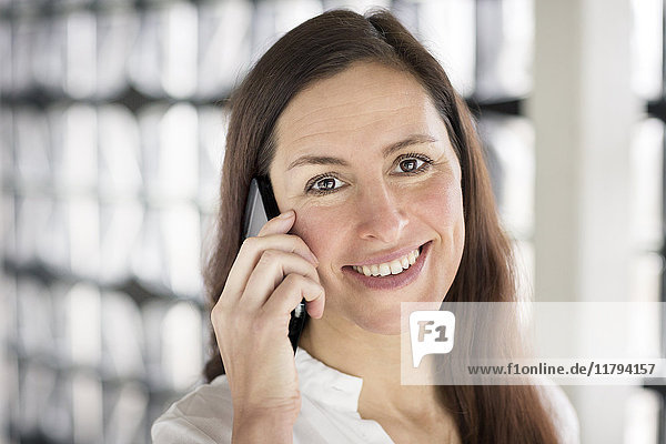 Porträt einer lächelnden Geschäftsfrau am Telefon