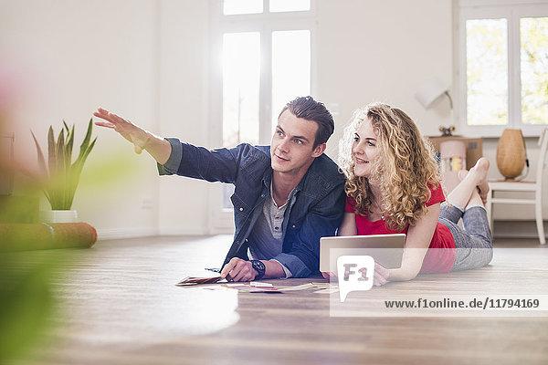 Junges Paar in neuem Zuhause auf dem Boden liegend mit Tablette aus Farbmusterauswahl