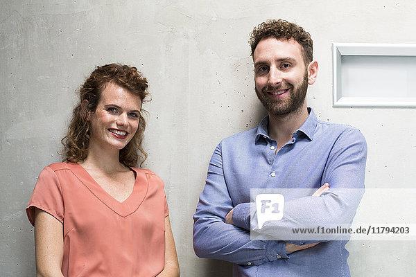 Porträt von lächelndem Mann und Frau an der Betonwand