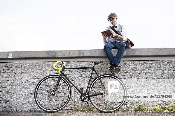 Geschäftsmann mit Fahrrad und Tafel an der Wand