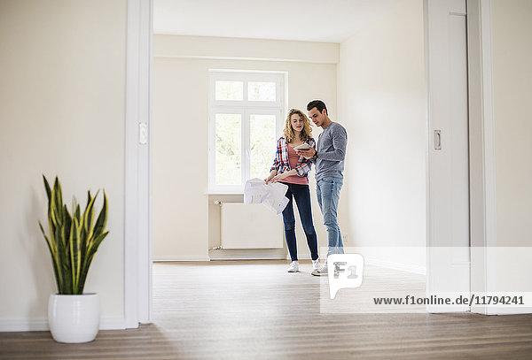 Junges Paar in neuem Zuhause mit Tablette und Grundriss