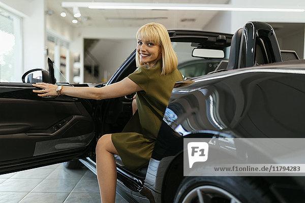 Blonde Frau wählt neues Auto im Autohaus