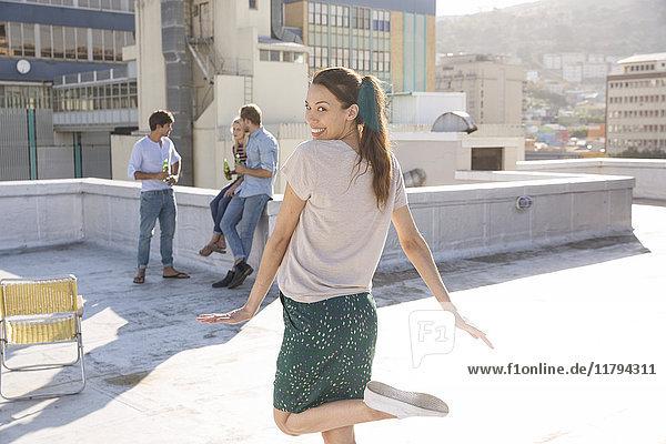Tanzende Frau auf der Dachterrasse mit Freunden im Hintergrund