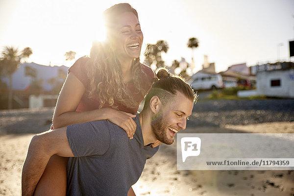 Junger Mann  der seiner Freundin eine Huckepackfahrt am Strand macht.