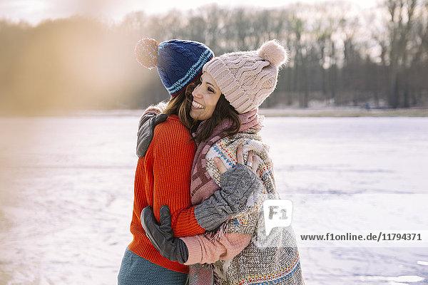 Freunde umarmen sich auf dem zugefrorenen See