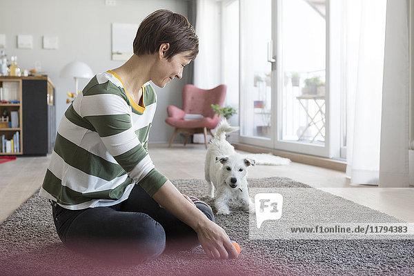 Lächelnde Frau  die zu Hause auf dem Boden sitzt und mit ihrem Hund spielt.