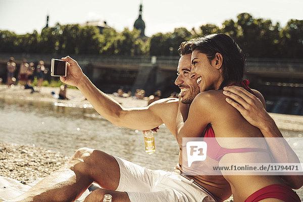 Verliebtes Paar nimmt Selfie am Strand mit.