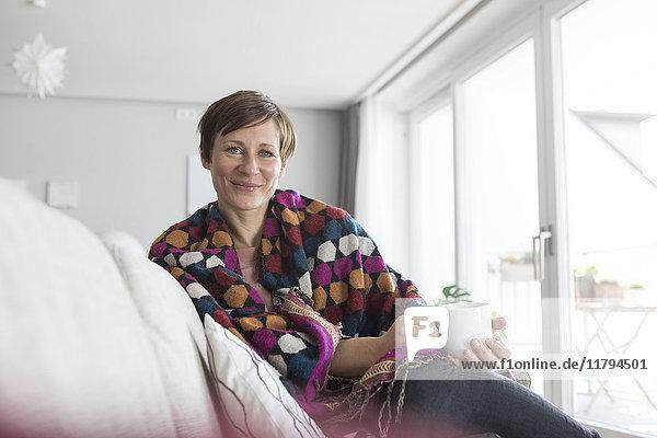 Porträt einer lächelnden Frau bei einer Tasse Kaffee auf der Couch
