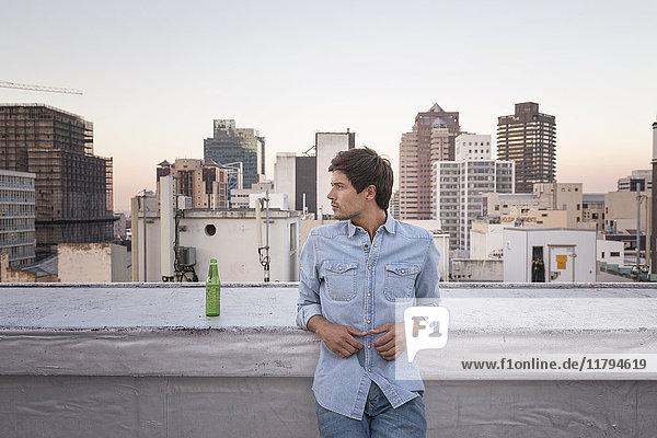 Zuversichtlicher junger Mann auf der Dachterrasse