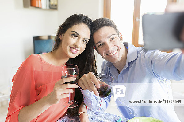 Paar hält Rotweingläser  die für einen Selfie posieren