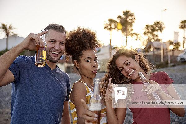 Drei Freunde mit Bierflaschen am Strand bei Sonnenuntergang