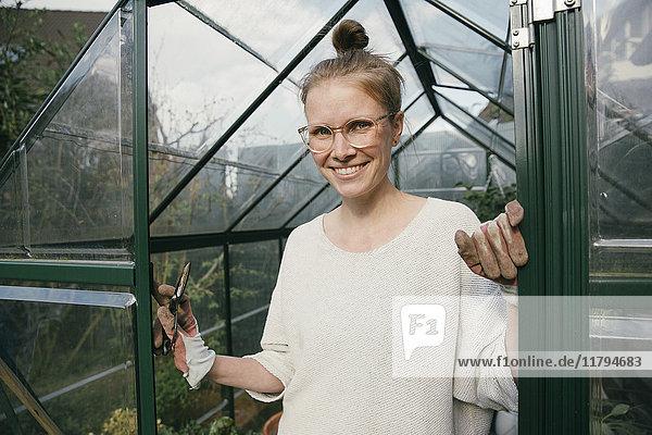 Porträt einer lächelnden jungen Frau  die in der Tür ihres Gewächshauses steht.