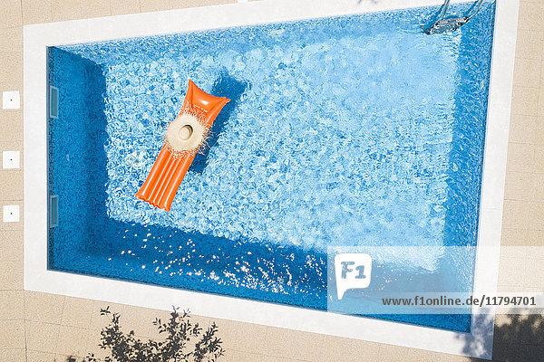 Strohhut auf orangefarbenem Luftbett im Schwimmbad  Draufsicht