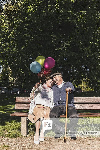 Glückliches Seniorenpaar mit Luftballons auf der Bank im Park