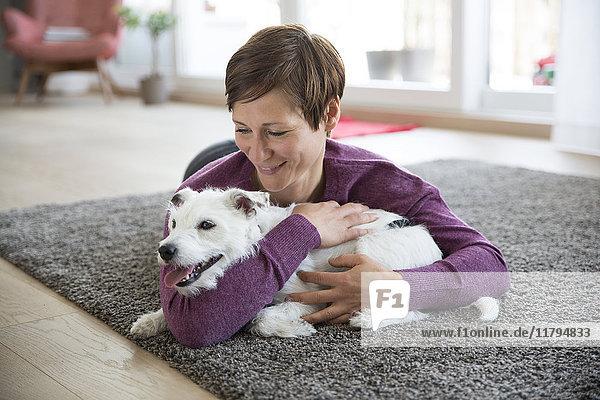 Frau  die auf einem Teppich im Wohnzimmer liegt und ihren Hund umarmt.