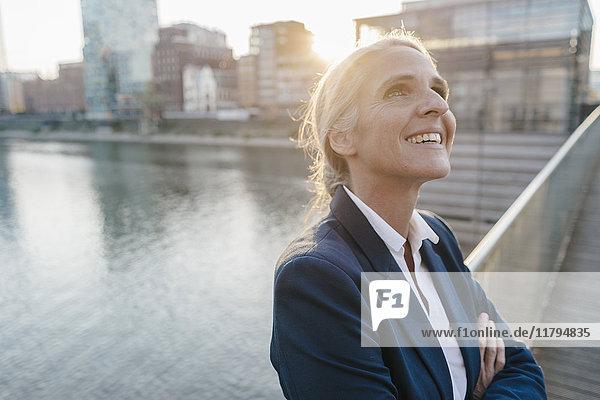 Lächelnde Geschäftsfrau auf der Brücke blickt nach oben