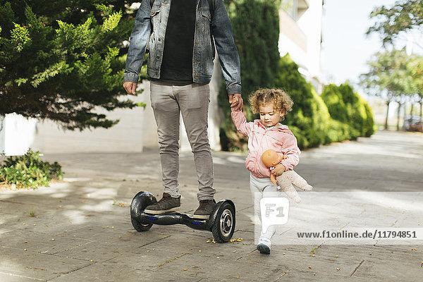 Vater auf Schwebeboard Hand in Hand mit seiner kleinen Tochter auf dem Bürgersteig