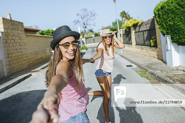 Happy friends holding hands on the street