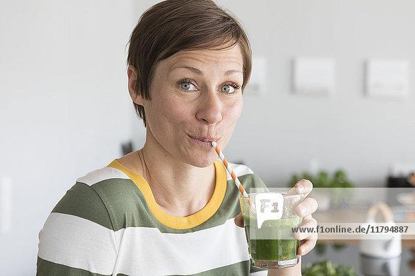 Porträt einer Frau  die in der Küche einen grünen Smoothie trinkt.