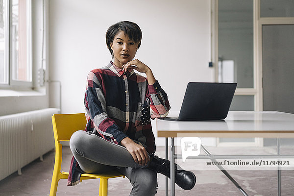 Confident young woman sitting on chair with laptop on table