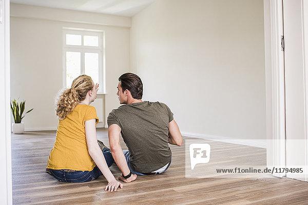 Junges Paar in neuem Zuhause sitzt auf dem Boden und diskutiert