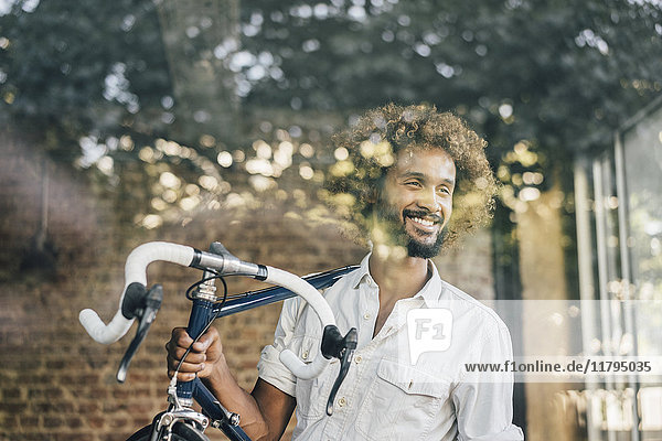 Smiling young man carrying bicycle