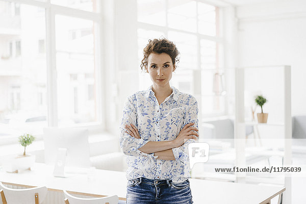 Businesswoman in office sitting on desk  looking confident