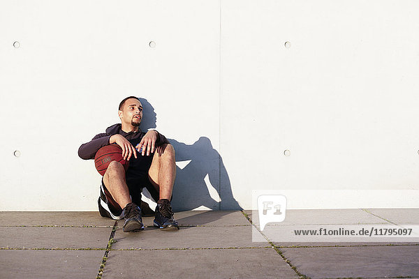 Young man with basketball having a break