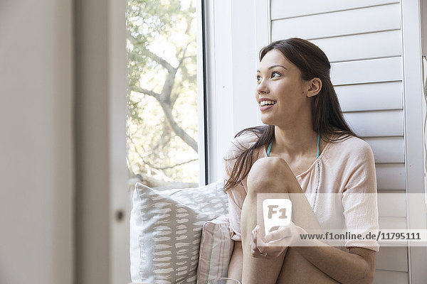 Smiling young woman sitting on windowsill