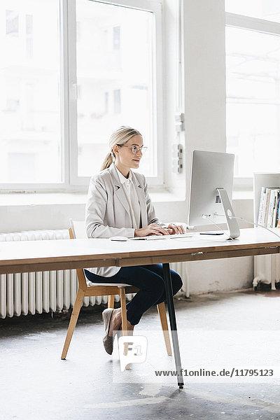 Geschäftsfrau sitzt am Schreibtisch und arbeitet mit dem Computer.