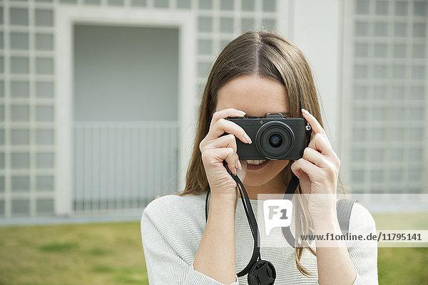 Junge Frau schaut durch die Kamera