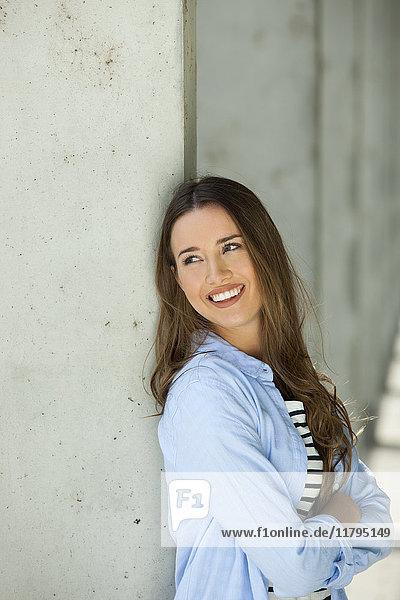 Porträt einer jungen Frau  die sich an eine Wand lehnt