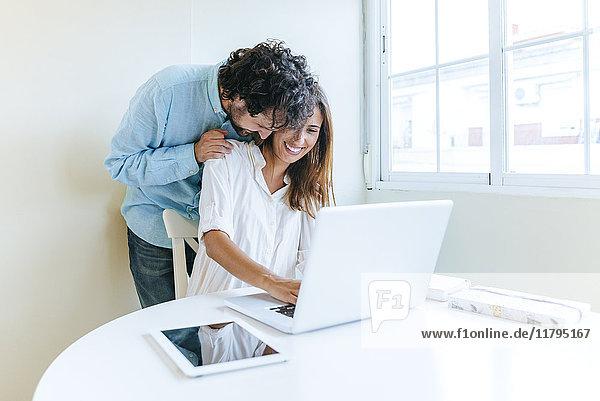 Mann umarmt Frau bei der Arbeit mit dem Laptop
