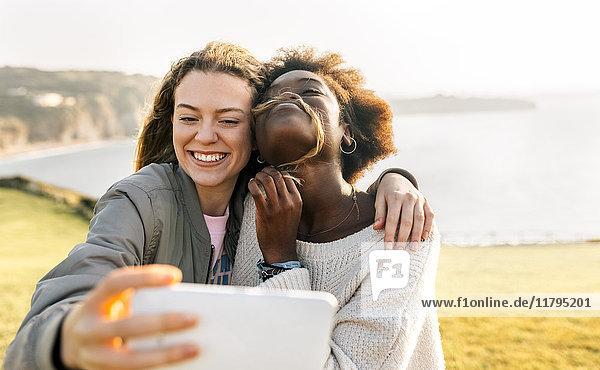 Zwei glückliche beste Freunde  die einen Selfie an der Küste machen.