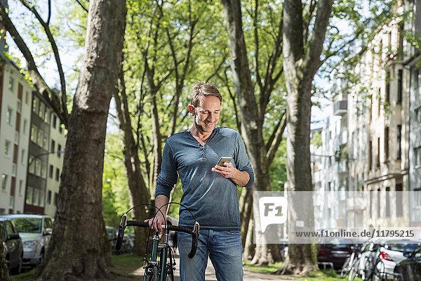 Lächelnder reifer Mann mit Fahrrad in der Stadt beim Blick aufs Handy