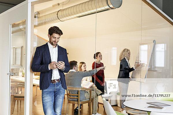 Geschäftsmann mit Handy im Büro mit Besprechung im Hintergrund