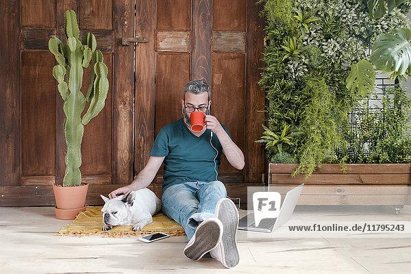 Der bärtige Mann sitzt mit seinem Hund auf dem Boden zu Hause und trinkt Kaffee. Der bärtige Mann sitzt mit seinem Hund auf dem Boden zu Hause und trinkt Kaffee.