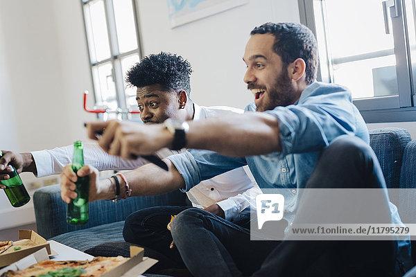 Aufgeregte Freunde mit Bierflaschen auf dem Sofa beim Jubeln