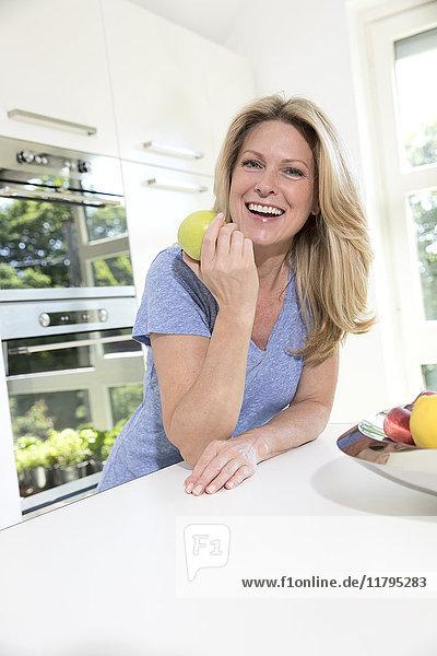 Porträt einer glücklichen Frau zu Hause beim Apfelessen