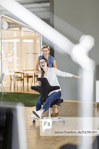 Verspielter Mitarbeiter schiebt Kollegen auf Bürostuhl