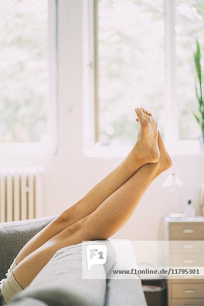 Beine einer Frau  die zu Hause auf der Couch liegt.