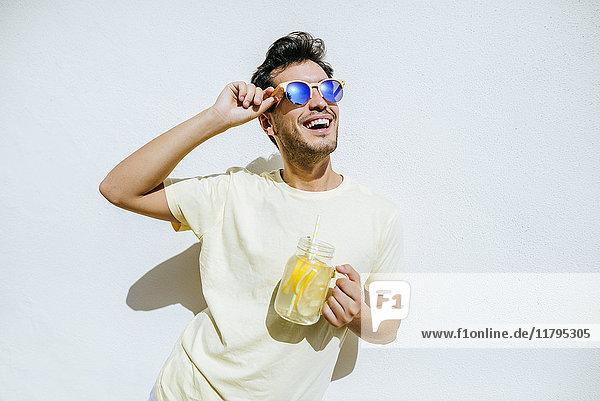 Jung und mit Sonnenbrille und Limonade in weißer Vorderwand